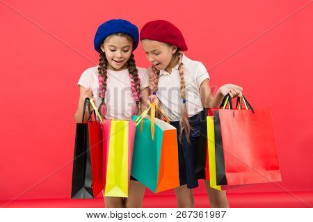 Shopaholic Concept. Signs You Are Addicted To Shopping. Kids Cute Schoolgirls Hold Bunch Shopping Ba