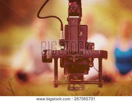 young videographer with gimball video slr rocording while healthy woman doing yoga exercise in the beautiful nature on the bank of the river