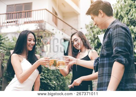 Asian People Enjoying Toasting Drinks Party Weekend With Holding Beer Clinking At Home Garden.