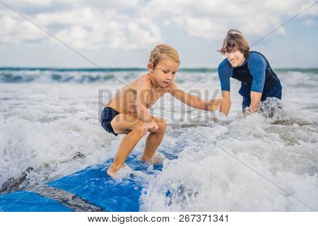 Father Or Instructor Teaching His 4 Year Old Son How To Surf In The Sea On Vacation Or Holiday. Trav