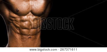 Muscular Male Torso On Black Background. Perfect Abs And Chest