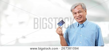 Portrait Of Happy Senior Asian Man Holding Credit Card And Showing On Hand Smiling And Looking At Ca