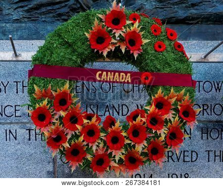 CHARLOTTETOWN, PE, CANADA - DEC. 8, 2017: A Remembrance Day wreath covered in poppies hanging on a Canadian war memorial.
