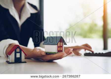 Woman Holds A House Model In Her Hand And Using Calculator . Buy Real Estate. Real Estate Services F