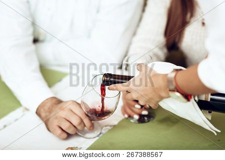 Girl Waiter In A Restaurant Pours Red Wine To Guys. The Concept Of Service Serving People In A Resta