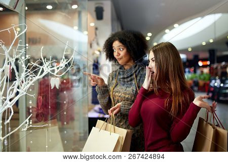 Young Multiethnic Diverse Race Women With Paper Shopping Bags Near Decorated Shopwindow. Girl Pointi