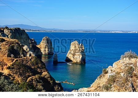 Lagos, Portugal - June 10, 2017 - Elevated View Of The Cliffs In The Ocean With Tourists In Kayaks I