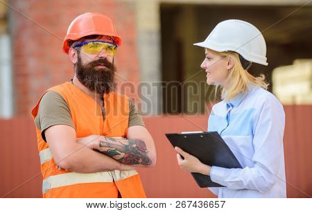Woman inspector and bearded brutal builder discuss construction progress. Construction project inspecting. Construction site safety inspection. Discuss progress project. Safety inspector concept poster