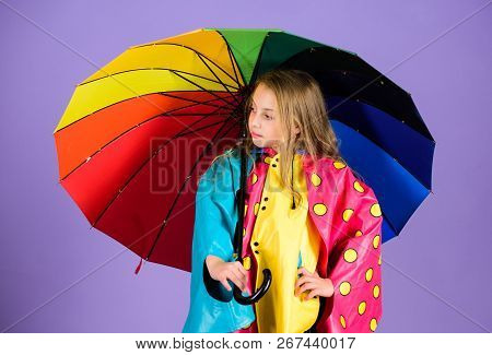 Waterproof accessories for children. Waterproof accessories make rainy day cheerful and pleasant. Kid girl happy hold colorful umbrella wear waterproof cloak. Enjoy rainy weather with proper garments poster