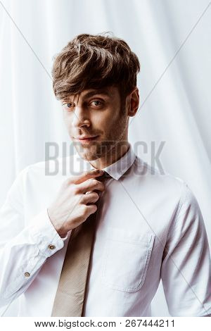 Portrait Of Handsome Businessman In White Shirt Looking At Camera And Tying Neck Tie