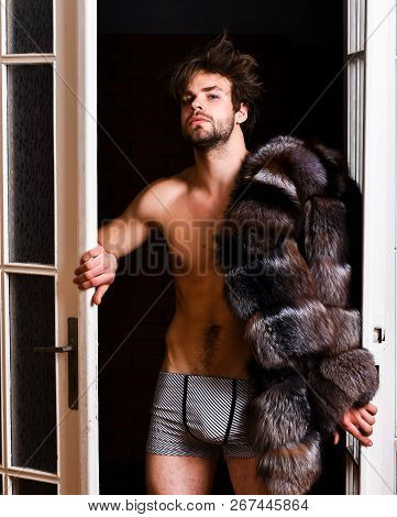 Richness and luxury concept. Luxury lifestyle and wellbeing. Luxury status symbol. Sexy macho tousled hair coming out bedroom door. Bachelor rich lover. Guy attractive posing fur coat on naked body poster