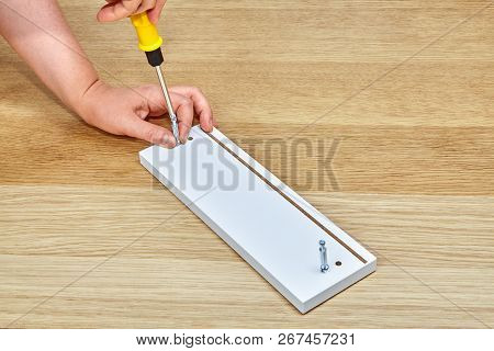 The Furniture Assembler Tightens The Connector Bolts Into A Piece Of Wooden Furniture With A Screwdr
