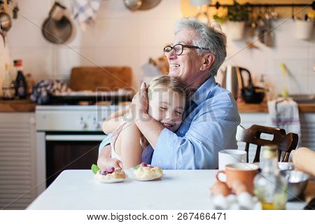 Happy grandmother is hugging granddaughter in cozy home kitchen. Family is cooking together. Senior woman and cute little child girl are smiling. Kid is enjoying kindness, warm hands, care, support. poster