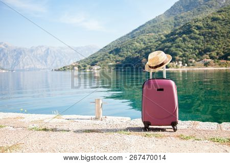 Pink Suitcase With Straw Hat On Sea Beach. Concept Of Travel, Vacation, Female Tourism, Trip, Journe