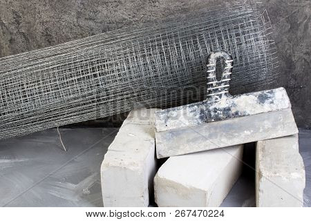 Roll Mesh For Plastering, Putty Knife Bricks, Hammer On The Gray Concrete Background. Copy Space. To