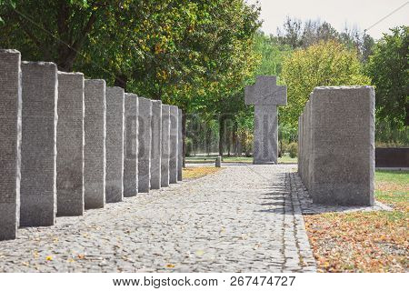 selective focus of identical headstones and stone cross at cemetery poster