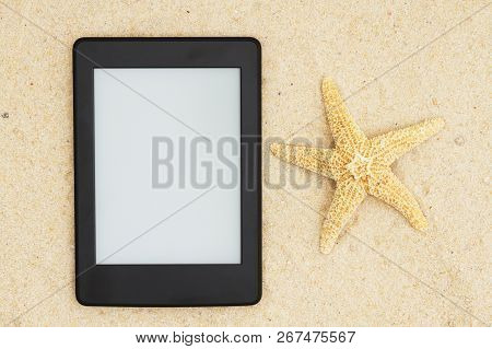 A Blank E-reader On The Beach For Your Summer Reading That You Can Use As A Mock Up For Your Message