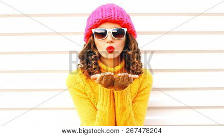 Funny Girl Blowing Red Lips Makes Sends Air Kiss Wearing Colorful Knitted Hat Over White Background