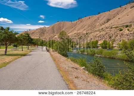 Sidewalk along the river and mountains.