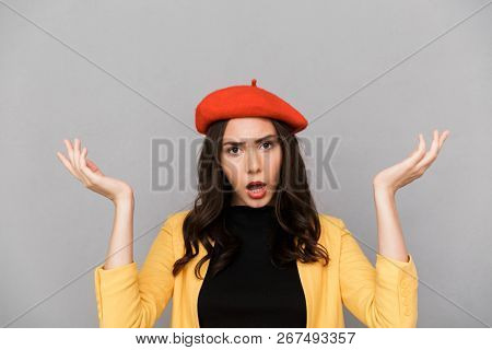 Close up of a confused young woman in red hat standing over gray background, shrugging shoulders