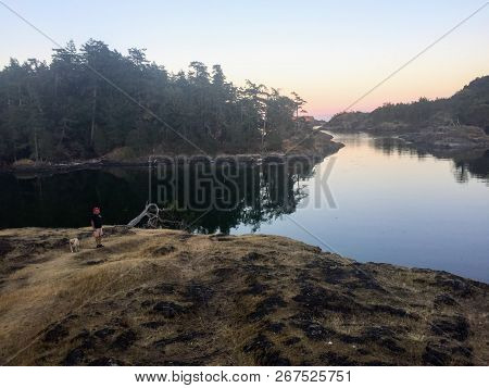 A Man Standing Along The Shores Of The Gulf Islands In British Columbia, Canada, Thinking And Contem