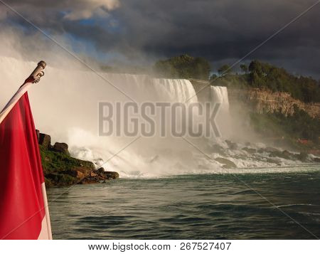 Majestic Falls In Niagara Falls . Gorgeous View Under A Blue Sky Canadian Flag Seen Next To Falls