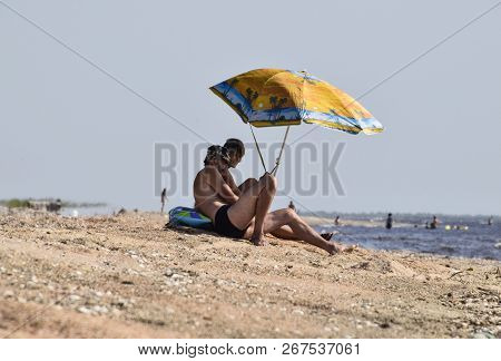 Anapa, Russia - July 17, 2017: Two Gay Men On The Beach Under An Umbrella. Homosexual Couple On The