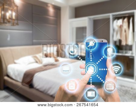 Smart Home Automation App On Mobile With Home Interior In Background. Internet Of Things Concept At