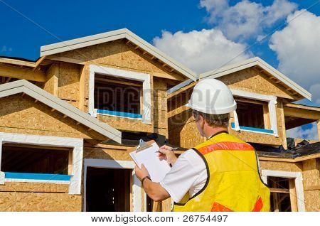 A man in a hard hat standing in front of an house holding a clipboard in his hand.