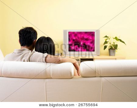 A couple watching television in the living room
