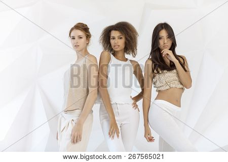Group Of Friends Of Different Race. Diverse Women Standing Together Against White Polygon Background