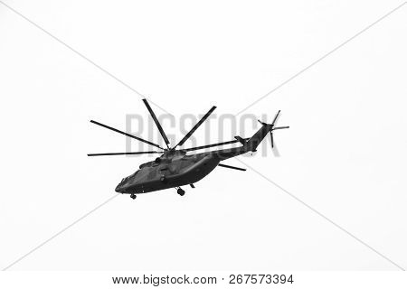 large military helicopter hovers in  sky. A camouflaged helicopter flies at high speed. poster