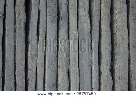 a gray blue vertical uneven concrete blocks. vertical lines. rough surface texture poster