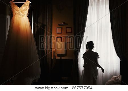 Gorgeous Bride Silhouette Standing At Stylish Wedding Dress, Hanging On Chandelier, In The Morning A