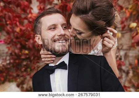 Gorgeous Bride And Stylish Groom Gently Hugging And Smiling At Wall Of Autumn Red Leaves. Happy Sens