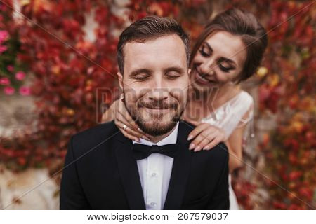 Gorgeous Bride Gently Hugging Stylish Groom At Old Wall Of Autumn Red Leaves. Happy Sensual Wedding