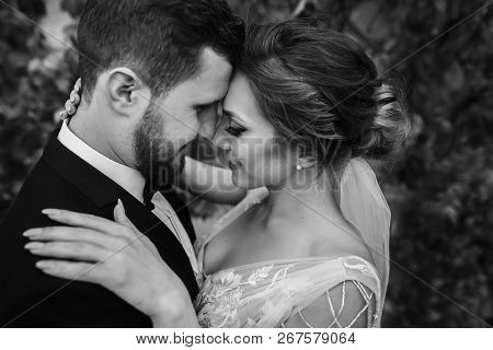 Gorgeous Bride And Stylish Groom Gently Hugging And Kissing Outdoors. Sensual Wedding Couple Embraci
