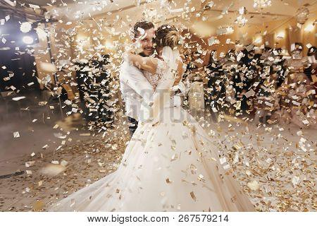 Gorgeous Bride And Stylish Groom Dancing Under Golden Confetti At Wedding Reception. Happy Wedding C