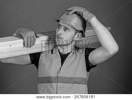 Man In Helmet, Hard Hat And Protective Gloves Holds Wooden Beam, Grey Background. Safety And Protect