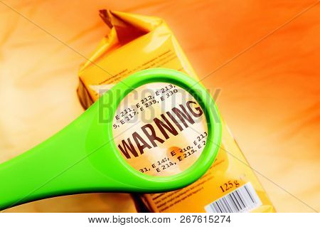 Magnifying Glass On Food Additives Label With Word Warning. Concept Warning Food Additives. Reading