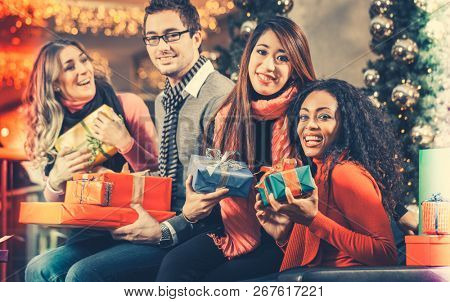 Diversity Friends with Christmas presents and bags shopping in mall with light decoration