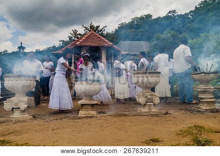 Kandy, Sri Lanka - July 19, 2016: White Clothed Buddhist Devotees Light Incense Sticks At The Temple