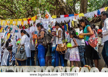 Kandy, Sri Lanka - July 19, 2016: White Clothed Buddhist Pilgrims Visit Wel Bodiya With Bodhi Tree D