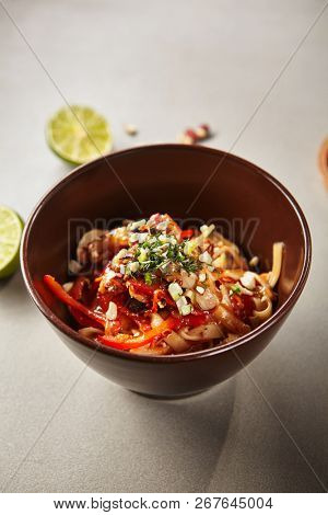 Chinese noodles with chicken and sauce on coconut milk. Asian style food concept. Colourful savory lunch looking appetizing on grey table