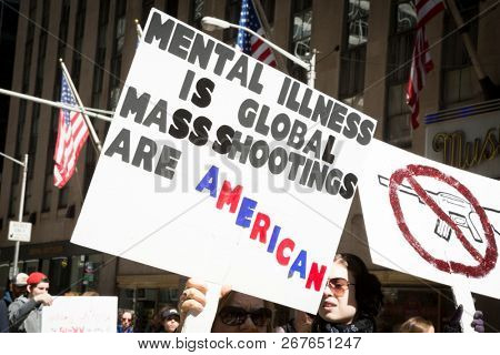 March For Our Lives: Close up of a sign that says MEntal Illness Is Global, Mass Shootings Are American held by a protestor during the march to end gun violence on 6th Ave, NEW YORK MAR 24 2018.
