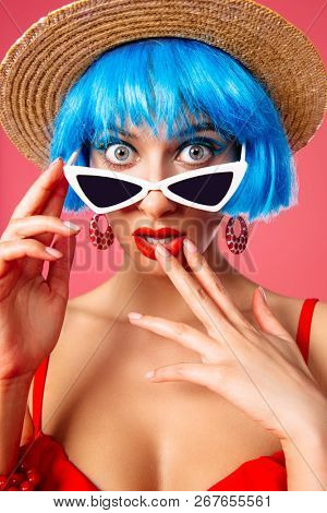 Close-up portrait of a funny girl with bright blue hair wearing pin-up sunglasses over pink background.  Beauty, fashion concept.  Pin-up style.