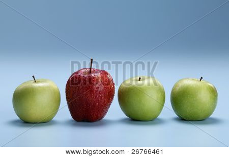Different concepts - red apple between green apples