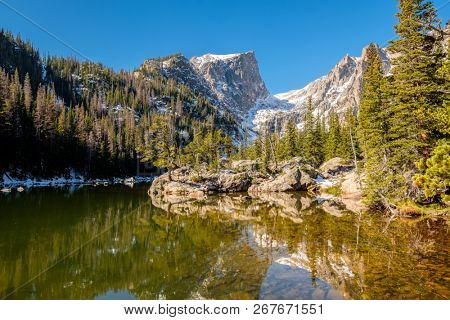 Dream Lake and reflection with mountains in snow around at autumn. Rocky Mountain National Park in Colorado, USA.
