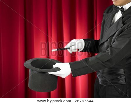 Hands of the magician with magic wand and top hat on stage.