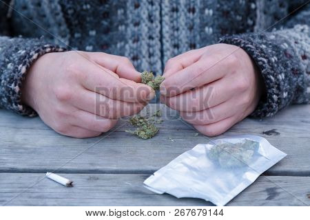 Close-up Of A Mans Hands Breaking Up Marijuana Buds Next To A Dispensary Bag And A Joint.